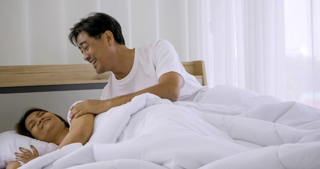 Happy asian couple sleeping together in a bedroom.