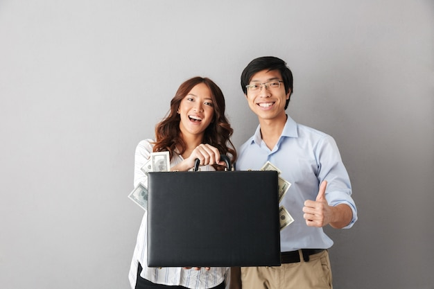 Happy asian couple standing isolated, holding briefcase full of money banknotes