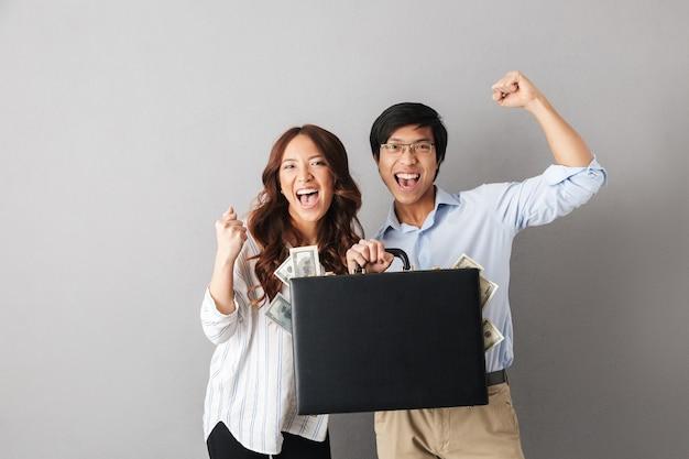 Счастливая азиатская пара стоя изолированно, держа портфель, полный денежных банкнот