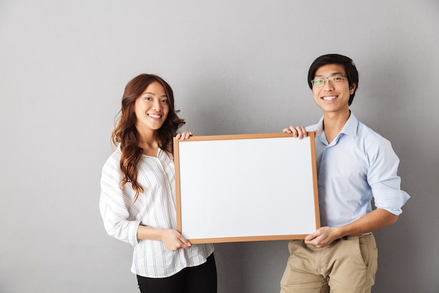 Happy asian couple standing isolated, showing blank board
