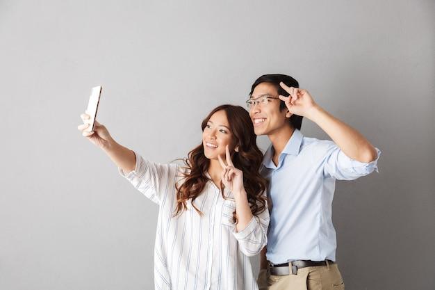 Счастливая азиатская пара стоя изолированно, принимая селфи с мобильным телефоном