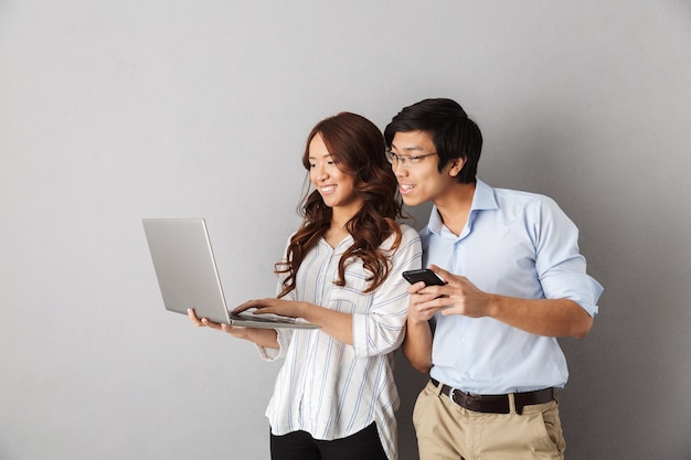 Happy asian couple standing isolated, using laptop computer, holding mobile phone