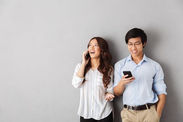 Счастливая азиатская пара стоя изолированно, используя мобильные телефоны