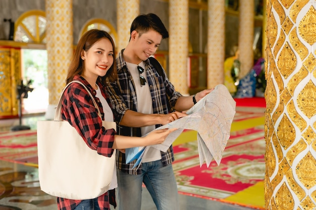 Happy asian couple tourist backpackers holding paper map and looking for direction while traveling in thai temple on holidays in thailand, handsome man pointing and checking map