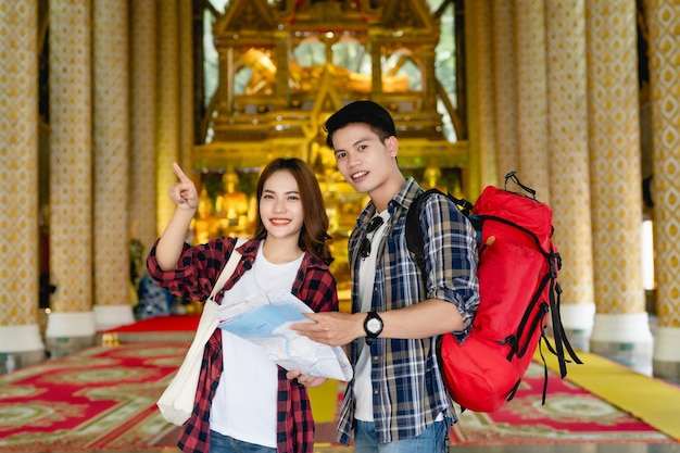 Happy asian couple tourist backpackers holding paper map and looking for direction while traveling in thai temple on holidays in thailand, pretty woman pointing target .