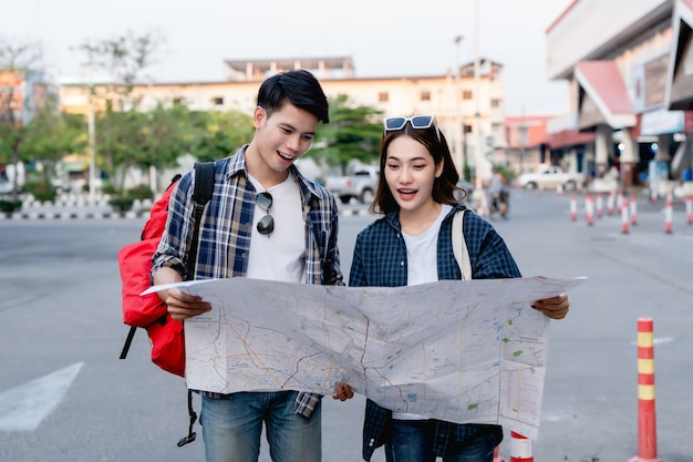 Happy asian couple tourist backpackers holding paper map and looking for direction while traveling, they smile with glad when arrived at location on paper map destination.