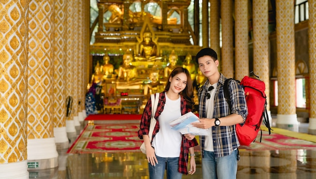 Happy asian couple tourist backpackers holding paper map while traveling in beautiful thai temple on holidays in thailand,
