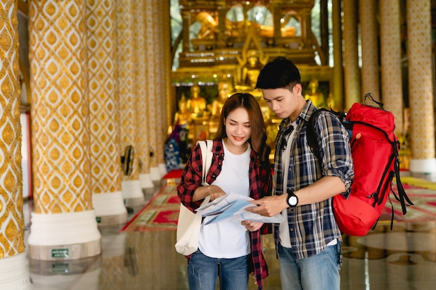 Happy asian couple tourist backpackers looking for direction on paper map while traveling in beautiful thai temple on holidays in thailand