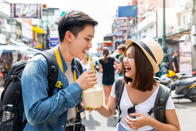 Happy asian couple tourist backpackers traveling in khao san road ,bangkok