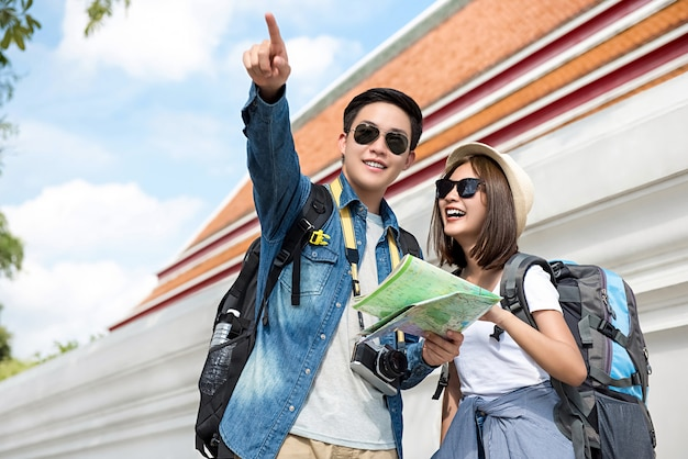 Happy asian couple tourist backpackers traveling