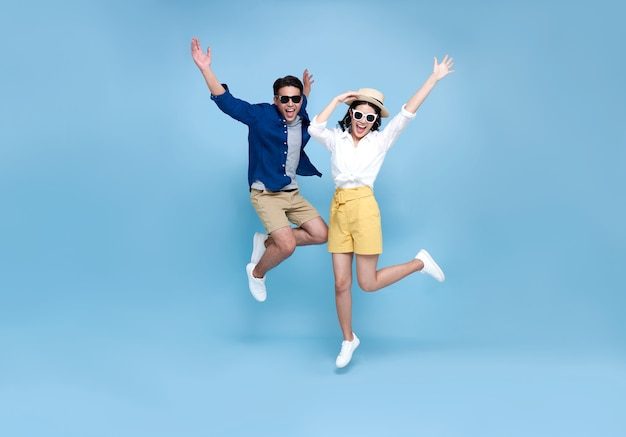 Happy asian couple tourist jumping celebrating to travel on summer holiday isolated on blue background.