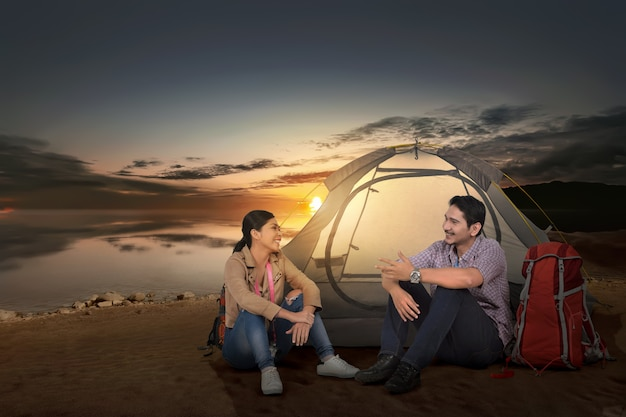 Happy asian couple traveler with tent enjoying sunset time