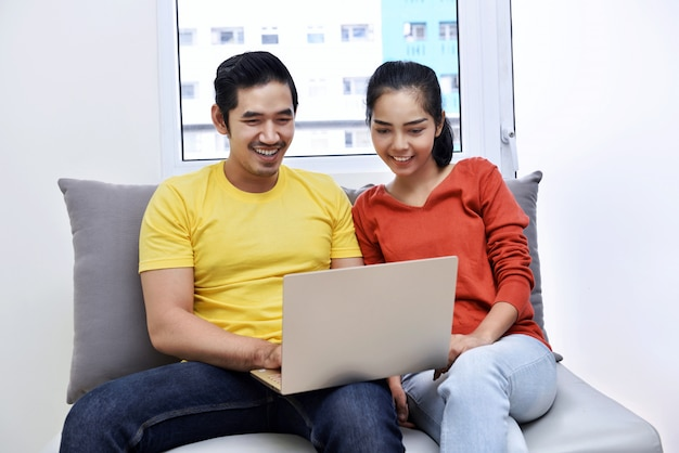 Happy asian couple using laptop while sitting on couch
