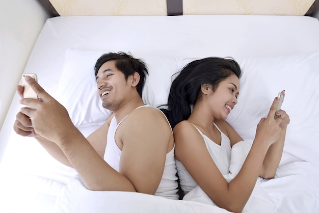 Happy asian couple with smartphones