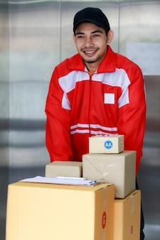 幸せなアジアの宅配便の男は、エレベーターからトロリーに段ボール箱のスタックをプッシュします。都市部の近代的な住宅ビルでの小包配達。 eコマースビジネスコンセプト。