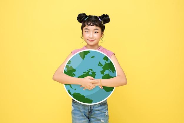 幸せなアジアのかわいい女の子の女子高生は、黄色の背景で隔離の地球を抱きしめます。世界環境デーのコンセプト。
