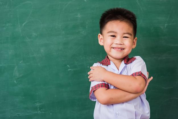 Happy asian cute little child boy from kindergarten in student uniform stand crossed arm smiling on green blackboard