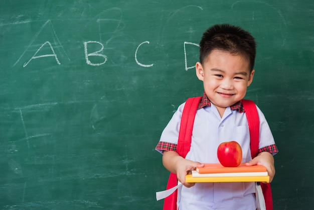 Happy asian cute little child boy from kindergarten in student uniform with school bag smile holding apple on books on green school blackboard