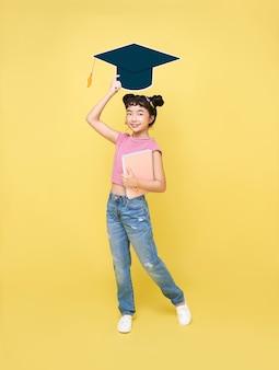 Счастливая азиатская милая школьница с выпускной шляпой и книгой, изолированными на желтом фоне.
