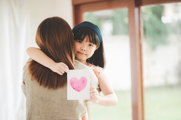 Happy asian daughter hugging her mother and giving her a postcard with a heart on it
