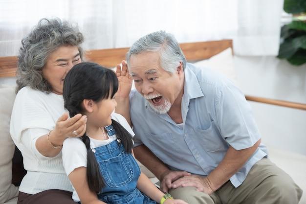 幸せなアジアの高齢者の幸せな祖父の頭がソファーに座っている間孫娘の頭に触れて、家で一緒に余暇を過ごします。