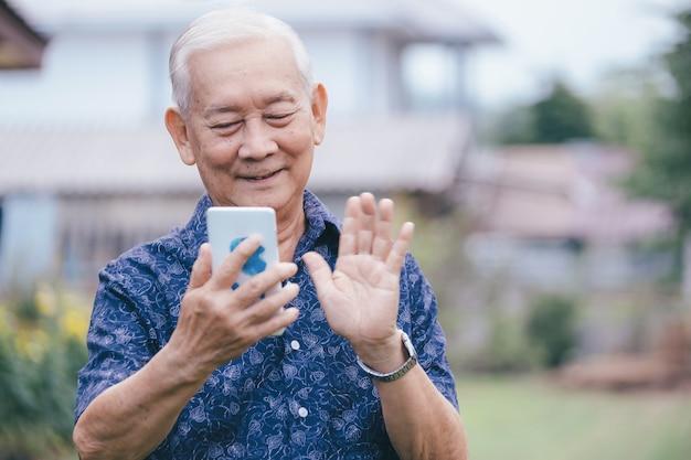 スマートフォンを使用して幸せなアジアの老人。写真を見ながら、モバイルアプリで大人の子供のための楽しい80年代の祖父の入力メッセージ。