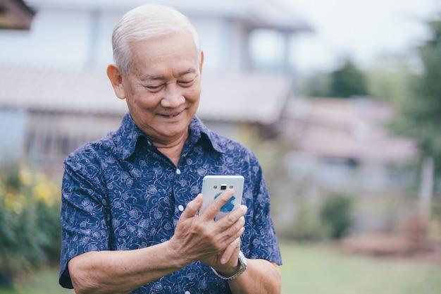 스마트 폰을 사용하는 행복 한 아시아 노인 남자. 유쾌한 80 년대 할아버지 타이핑 메시지를 모바일 앱에 담아 사진을 감상하세요.