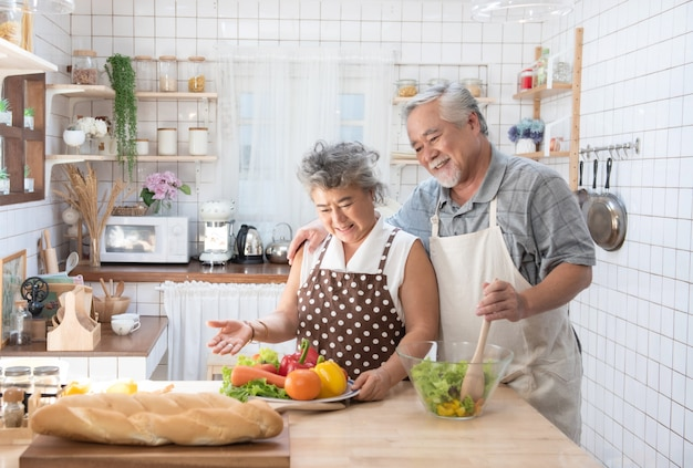 Happy asian elder senior couple cooking fresh meal in kitchen at home.