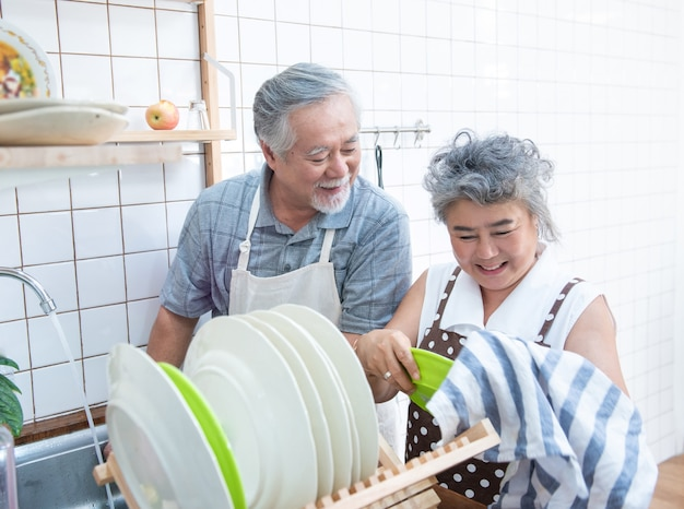 Happy asian elder senior couple washing dishes in sink at home in kitchen at home.