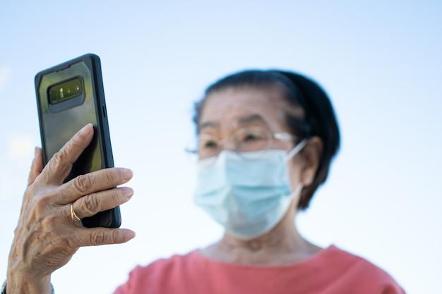 Счастливые азиатские пожилые люди в маске для лица и отвечая на видеозвонок, используя свой смартфон в парке и беседуя с семьей, технологией и концепцией пожилых людей.