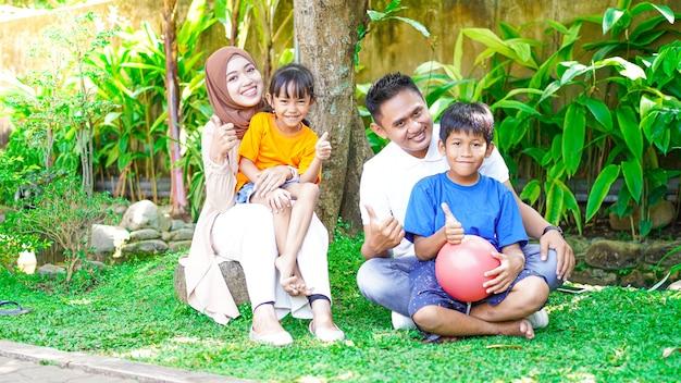 행복 함 아시아계 가족이 놀고 정원에서 함께 채팅
