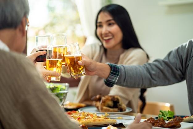 幸せなアジアの家族は昼食時に一緒に歓声を上げます