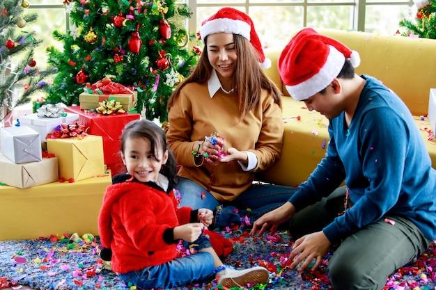 Счастливая азиатская семейная дочь носит свитер, сидя с мамой и папой в красно-белой шляпе санта-клауса, играя, захватывающе смеясь, когда дует вечеринку поппер с конфетти из блестящей бумаги вокруг пола в рождество.