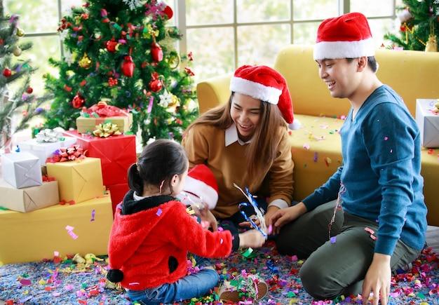 Счастливая азиатская семейная дочь носит свитер, сидя с мамой и папой в красно-белой шляпе санта-клауса, играя, захватывающе смеясь, когда дует вечеринку поппер блестящие бумажные конфетти вокруг пола в рождество.
