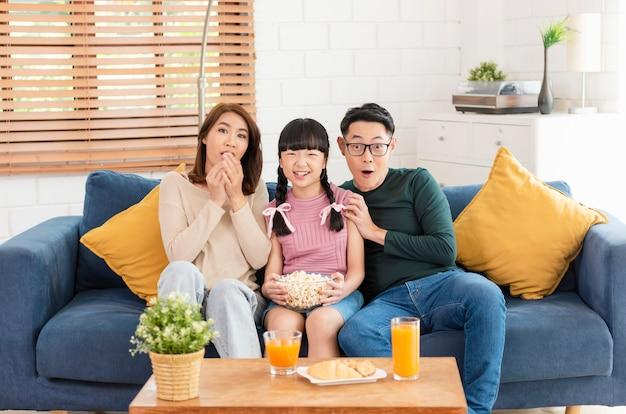 ポップコーンを食べて、自宅のリビングルームのソファで一緒にテレビを見ている幸せなアジアの家族。レジャーと人々の概念。