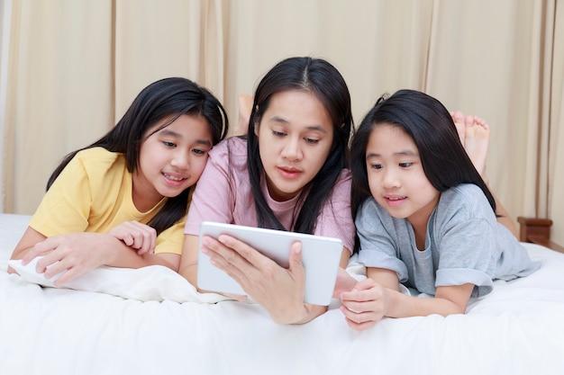 幸せなアジアの家族は寝室のベッドで楽しんでリラックスする母と娘は一緒にタブレットを使用して楽しむ