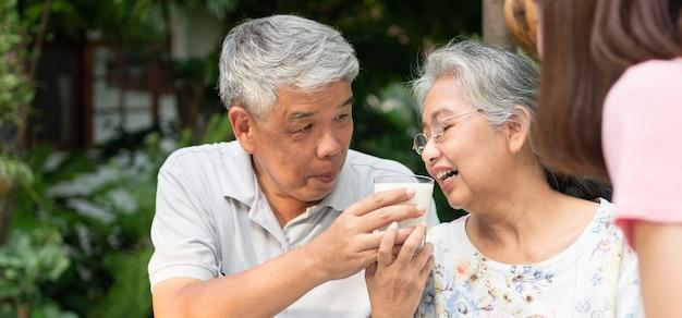 幸せなアジアの家族は裏庭で一緒に昼食を楽しむ夫はミルクの妻を養う