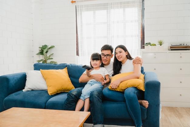 幸せなアジアの家族は彼らの自由な時間を家で一緒にリラックスして楽しんでいます