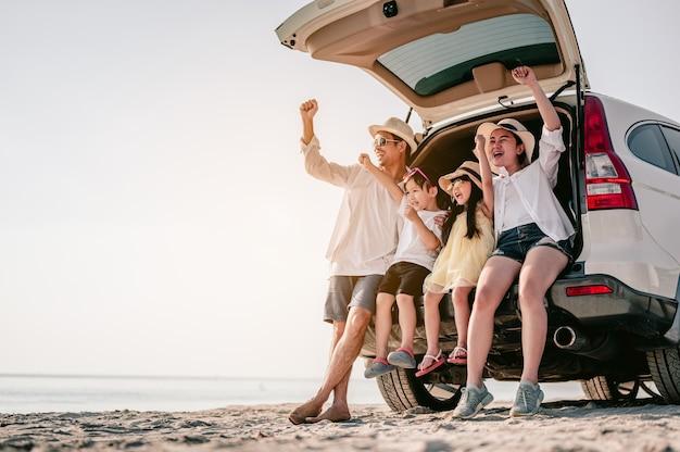 좋아하는 자동차로 해변 여행을 즐기는 행복한 아시아 가족 부모와 아이들이 여행 중입니다