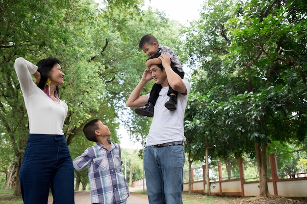 Happy asian family enjoying family time together in the park. family concept