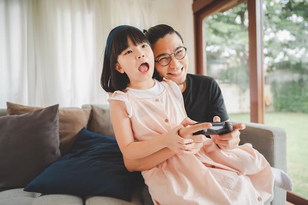 幸せなアジアの家族は、リビングルームでビデオゲームコントローラーを使用して笑い、一緒にビデオゲームをプレイする父と少女の娘を興奮させました