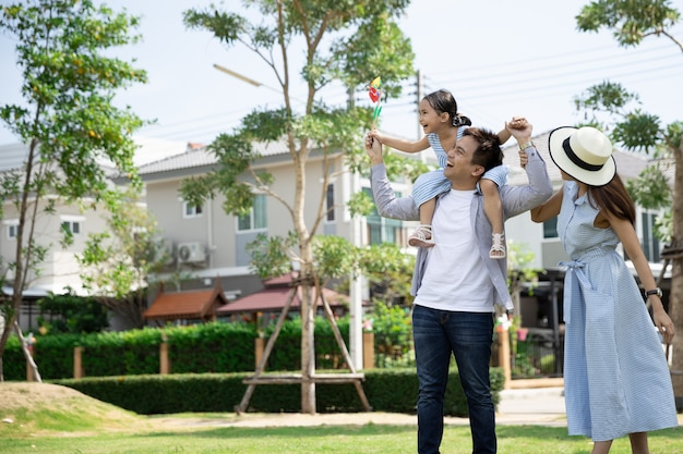 Happy asian family. father gave his daughter a piggyback at a park at natural sunlight and house. family vacation concept
