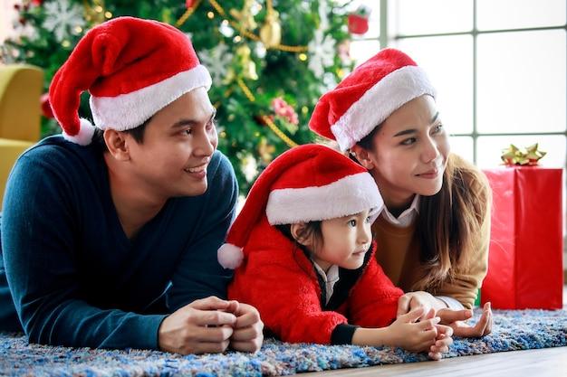 Счастливая азиатская семья, отец, мать и дочь носит свитер с красной и белой шляпой санта-клауса, лежа на ковровом покрытии, празднуя канун рождества вместе в передней декорации рождественская сосна.
