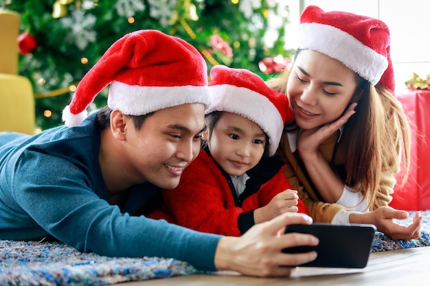 Счастливый азиатский семейный отец, мать и дочь носит свитер с красно-белой шляпой санта-клауса, лежащий на ковровом покрытии, используя камеру смартфона, делающую селфи-фото, вместе празднуя канун рождества.