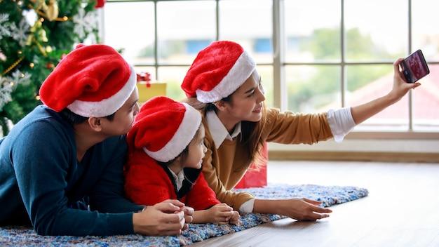 Счастливая азиатская семья, отец, мать и дочь носит свитер с красной и белой шляпой санта-клауса, лежа на ковре. мама с помощью камеры смартфона делает селфи-фото, празднуя канун рождества.
