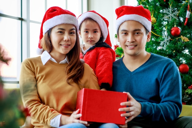 Счастливая азиатская семья, отец, мать и дочь носит свитер с красной и белой шляпой санта-клауса, улыбаясь, смеясь, держа настоящую подарочную коробку, готовьтесь распаковать ее вместе, празднуя канун рождества.