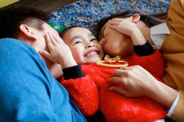 Счастливая азиатская семья, отец, мать и дочь носит свитер с красным, лежа на ковровом покрытии, вместе празднуя канун рождества.