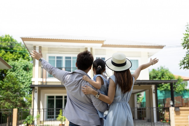 Happy asian family. father, mother and daughter near new home. real estate