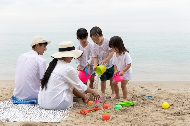 幸せなアジア家族5人夏休みにビーチで砂の上でおもちゃを一緒に遊んで朝の時間で、日の出。休日と旅行のコンセプトです。