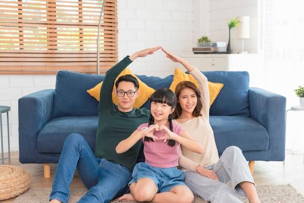 幸せなアジアの家族は、自宅のリビング ルームのソファで一緒に新しい建物の住宅をジェスチャーします。保険保護のコンセプト